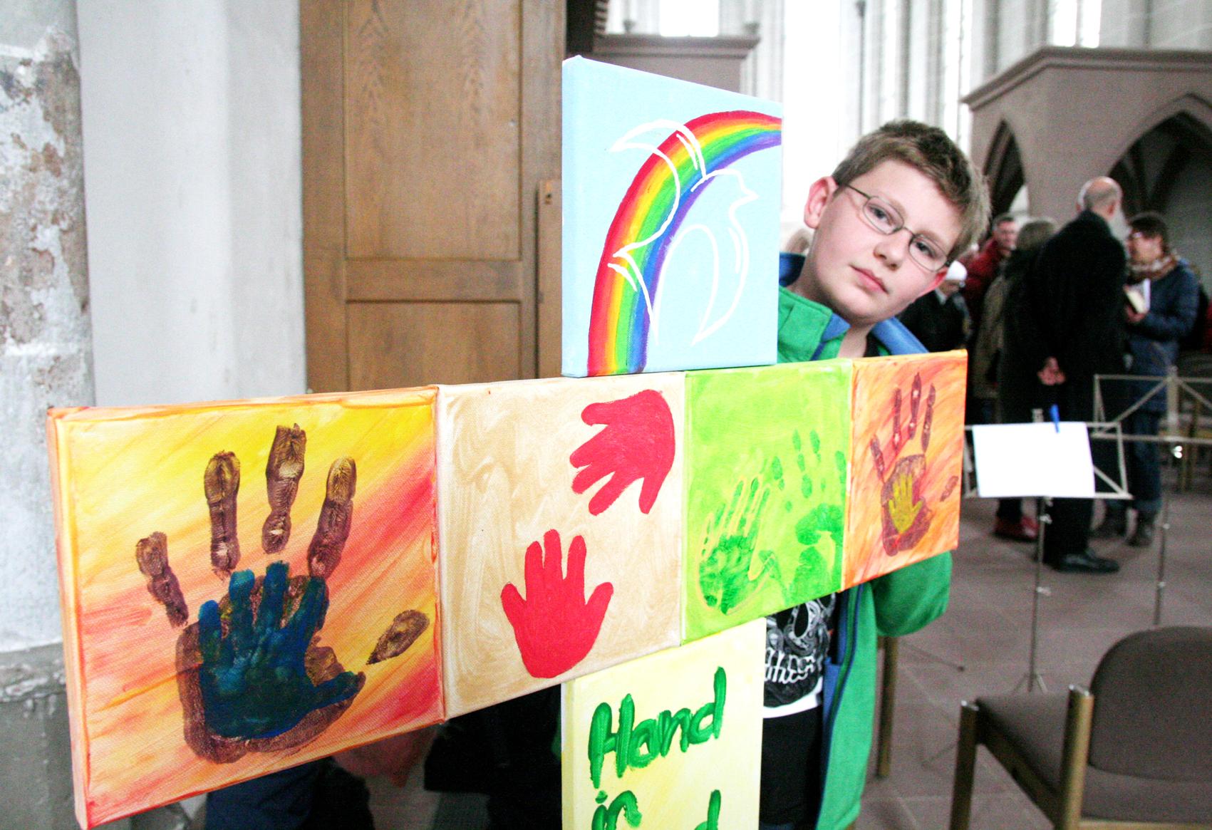 """Begeistert mitgemacht: Ausstellungsbesucher Leon Franke (12) gefällt das Kreuz der Spielgruppe """"Hand in Hand""""."""