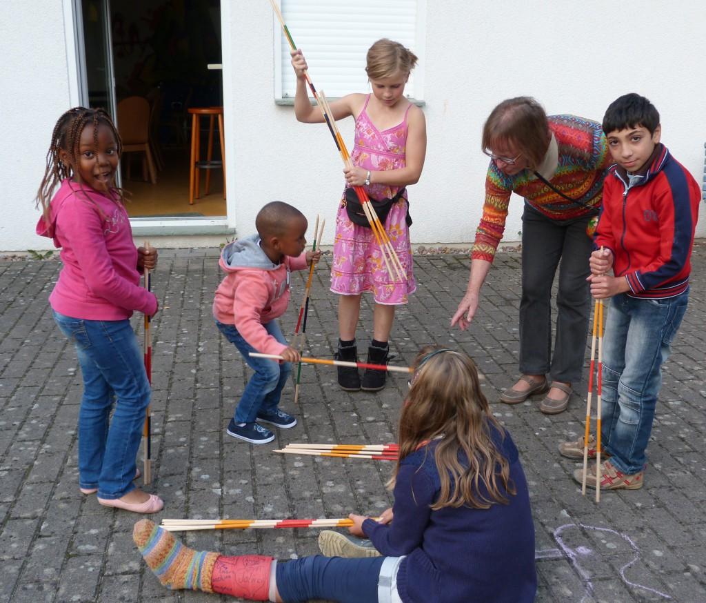 Gemeinschaft: Gunhild de Faria spielt mit den Kindern im Pfarrgarten Mikado.