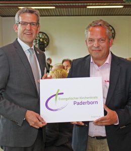 Stellen das neue Logo des Evangelischen Kirchenkreises Paderborn vor: Superintendent Volker Neuhoff (l.) und Detlef Jakobsmeyer (Agentur RLS jakobsmeyer). Foto: EKP/Heide Welslau