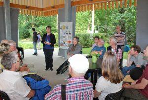 Vielfalt im GlaubensGarten: Pfarrerin Antje Lütkemeier (stehend) erläuterte das Projekt und führte die Umweltbeauftragten durch die sieben Gärten der beteiligten Religionen. Foto: EKP/Oliver Claes.