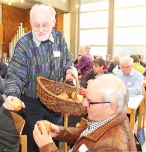 Der Initiator der Apfelbaum-Aktion im Reformationsgedenkjahr 2017, KSV-Mitglied Wolfgang Dzieran, verteilt Äpfel an die Synodalen. FOTO: OLIVER CLAES