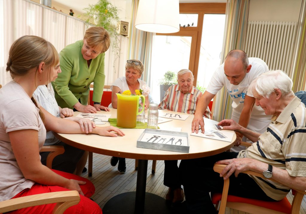 Bundeskanzlerin Angela Merkel und Altenpfleger Ferdi Cebi Im Sophie Cammann-Haus, Einrichtung für Demenzkranke, im Gespräch mit Bewohnern. Foto: Hilla Südhaus