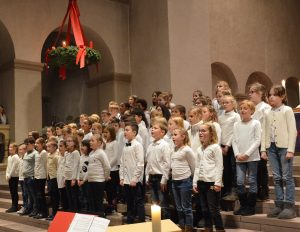 Schülerinnen und Schüler singen gemeinsam beim Christingle-Gottesdienst in der Abdinghofkirche.