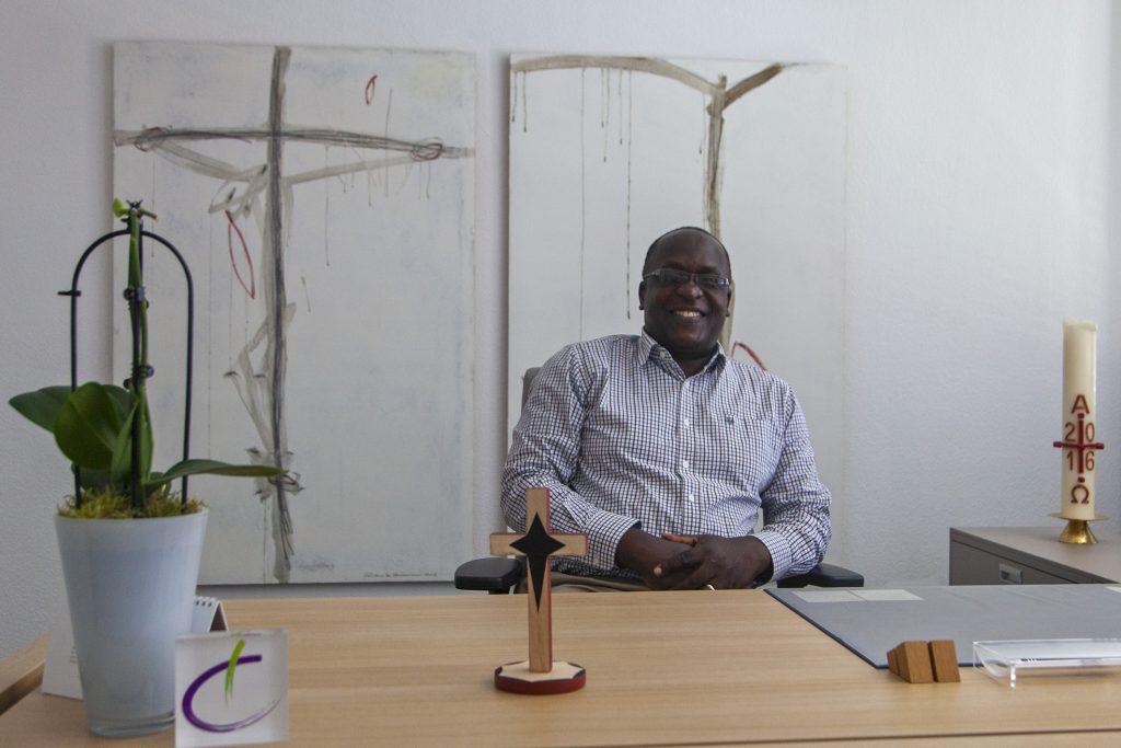 Gut gelaunt: Superintendent Frederick Muganyizi am Schreibtisch seines Kollegen Volker Neuhoff. Das Holzkreuz aus Tansania hat schon seinen Platz gefunden. Foto: Wolfgang Dzieran