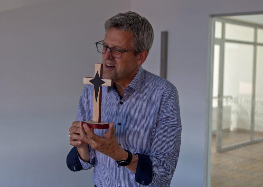 Gastgeschenk: Superintendent Volker Neuhoff mit einem Holzkreuz, das ihm sein Kollege Frederick Muganyizi geschenkt hat. Foto: Wolfgang Dzieran
