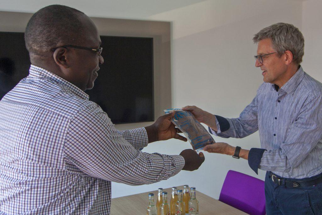 Gastgeschenk: Superintendent Frederick Muganyizi übergibt einen Beutel mit Instant-Kaffee, der in Bukoba im Kirchenkreis Kusini B hergestellt wird, an Superintendent Volker Neuhoff. Foto: Wolfgang Dzieran