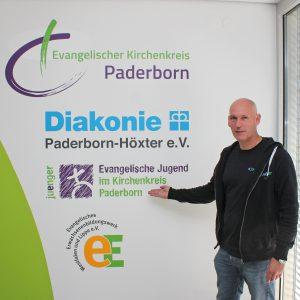 Jugendliche wollen mitbestimmen und verlässliche Beziehungen erleben, weiß der Jugendreferats-Leiter Oliver Schwarz, hier vor dem Logo der Ev. Jugend im Haus der Evangelischen Kirche in Paderborn. FOTO: HEIDE WELSLAU