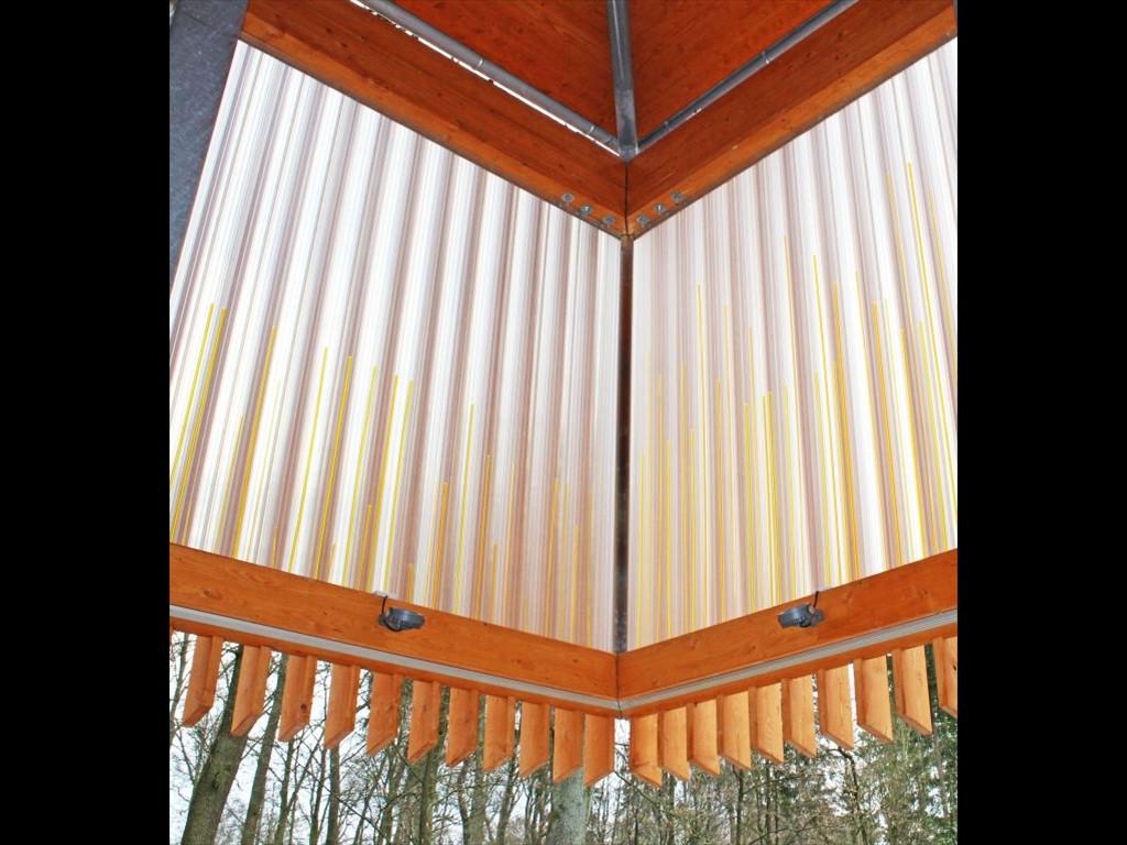 Der Pavillon ist eine Konstruktion mit Fichtenholz und künstlerisch verarbeiteten Leuchtstäben aus Acryl. Betont wird jeweils die Senkrechte – passend zu den Bäumen im Kurwald.