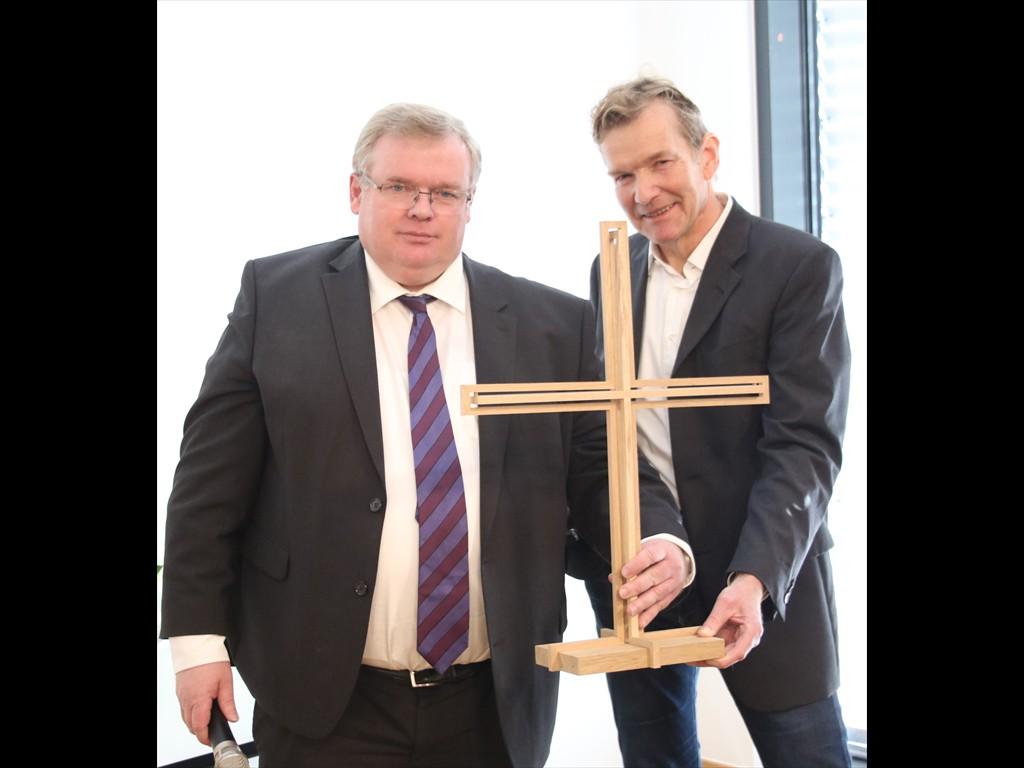 Architekt Reinhard Michel (r.) überreicht Superintendent Frank Schneider das selbstgefertigte Holzkreuz