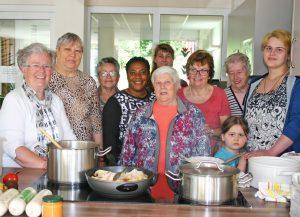 Der Kochkurs rund um Organisatorin Helga Weber-Kruck (links) und den Ehrenamtlichen Angelika Dirks (3. v. rechts.) und Desiree Matthes (4. v. rechts - hinten) ist von Alter und Herkunft her bunt gemischt. FOTO: MAYA S. MANGIACAPRA/JOHANNESWERK