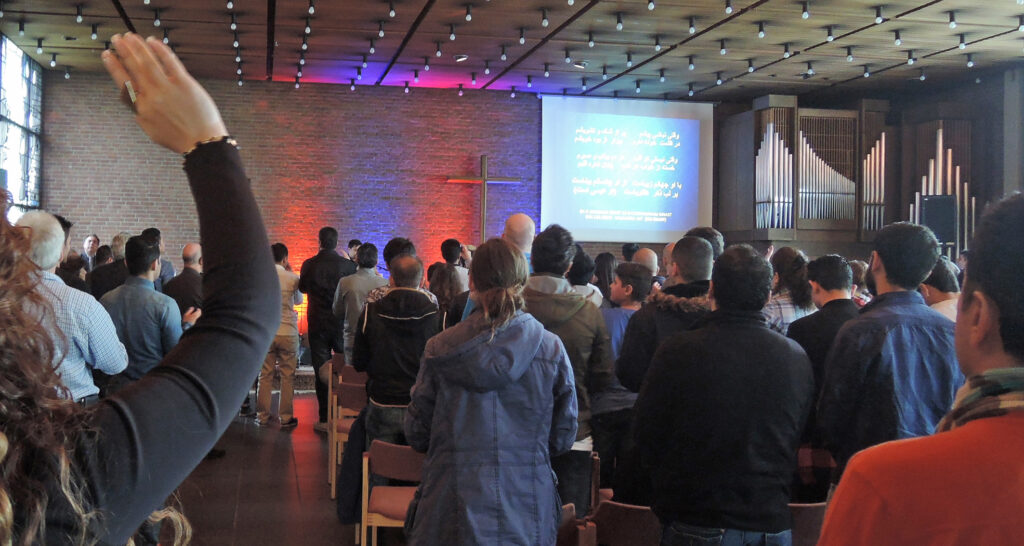 """""""Praise Night"""": Persischsprachige Christinnen und Christen beim Singen während einer Veranstaltung im Lukaszentrum. Foto: Christoph Keienburg"""
